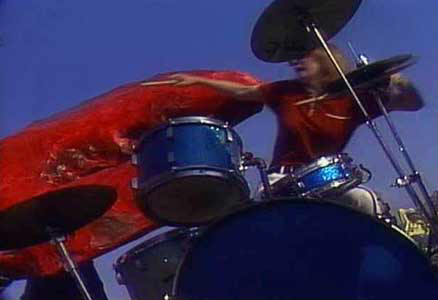 Crystal at the Trixon drumkit being attacked by a mutated lobster in a scene from the cult film 'Lobsteroids'